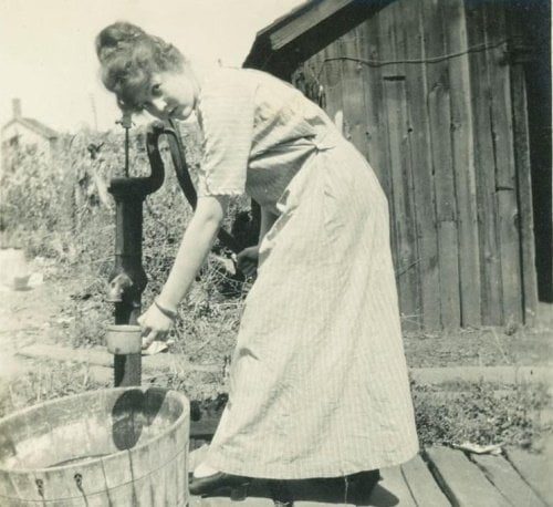 Woman pumping water from a hand well, vintage photo